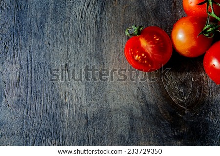Close-up of fresh, red ripe cherry tomatoes on wooden surface, top view - stock photo