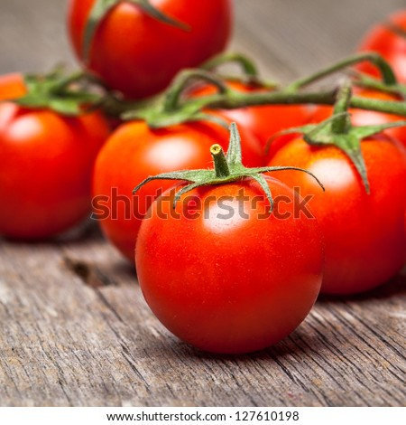 Close-up of fresh, ripe cherry tomatoes on wood - stock photo