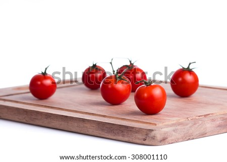 Close-up of fresh, ripe tomatoes on wooden cutting board. - stock photo