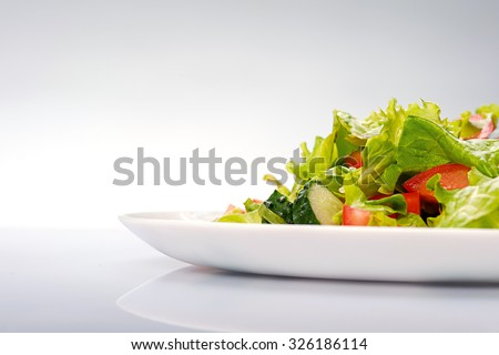 Close up of fresh salad of lettuce, cucumber and tomato on plate for healthy eating. Isolated on blue background - stock photo