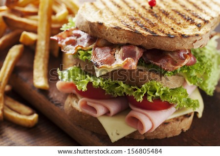 close up of fresh sandwich with ham, bacon,tomatoes,cheese and lettuce - stock photo