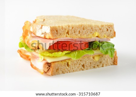 close up of fresh sandwich with ham, cheese and vegetables on white background