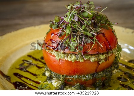 Close up of fresh tomato tower appetizer filled with olive tapenade sitting on ricotta cheese, balsamic vinegar and olive oil and garnished with microgreens sitting on rustic yellow plate - stock photo
