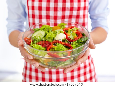 Close-up of fresh vegetable salad in bowl held by female in apron - stock photo