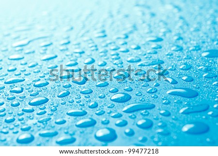 Close-up of fresh water drops on blue surface which can be used as background or texture.Small depth of field and back lighting. - stock photo