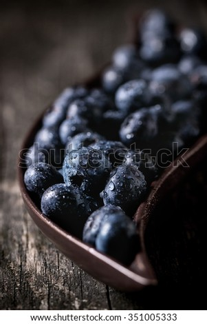 Close up of fresh wet blueberries in decorative ceramic plate over old wooden table