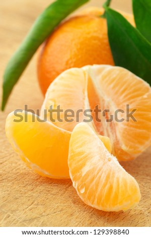Close-up of fresh whole tangerine and slices on wood. - stock photo