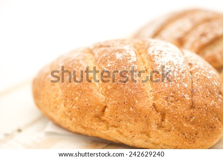 Close up of freshly baked loft of bread for healthy breakfast diet put on wooden table on white background - stock photo