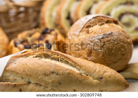 Close up of freshly baked whole wheat grain bread and loaf on cutting board for a healthy diet background  - stock photo