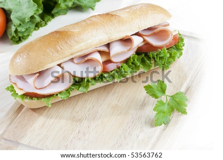 Close up of freshly made sandwich on wooden board - stock photo