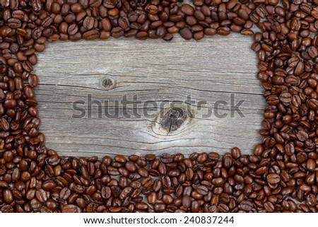 Close up of freshly roasted coffee whole beans, forming a rectangle shape, on rustic naturally aged wood  - stock photo