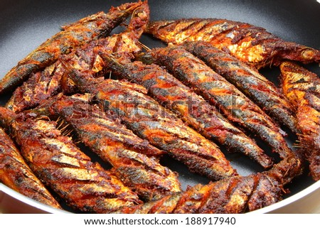 Close up of fried fish in the pan.  - stock photo