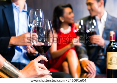 Close up of friends chatting and drinking red wine