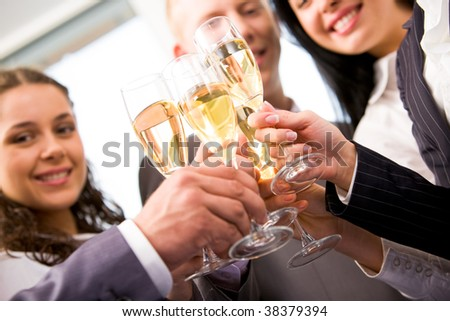 Close-up of friends hands holding glasses with champagne and making cheers - stock photo