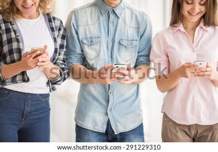 Close-up of friends using their phones and having fun together. - stock photo