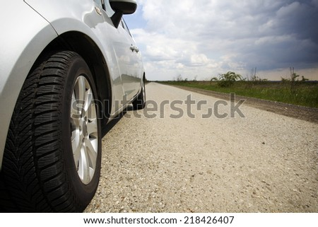 Close-up of front wheel of the car on narrow road in countryside with clouds in background