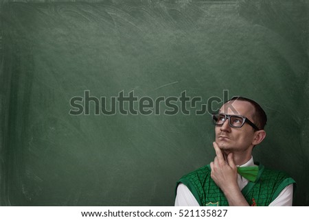 Close up of funny nerd thinking over chalkboard with copy space