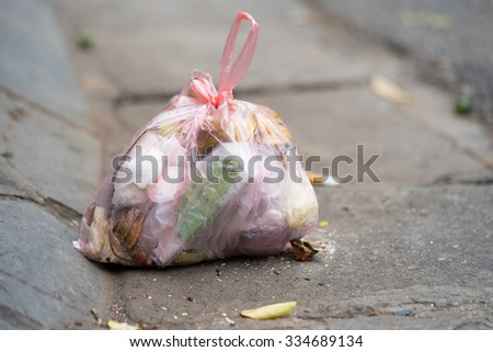 Close up of garbage held in a polymer bag being thrown to the street in an Asia city. - stock photo