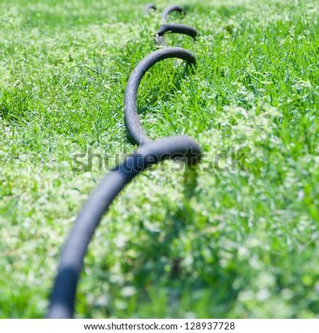 Close up of garden hose in grass, selective focus, shallow dof - stock photo