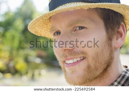 Close-up of gardener smiling while looking away - stock photo