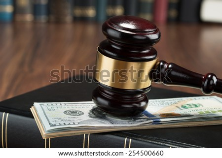 Close-up Of Gavel On A Stack Of American Banknote And Law Book - stock photo