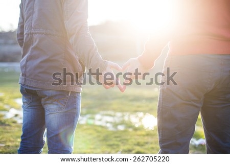 Close up of gay couple making heart shape with hands - stock photo
