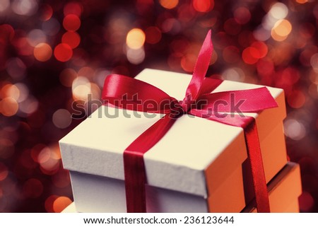 Close up of gift box with red bow on abstract background - stock photo