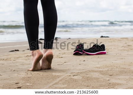 Close-up of gil's bare feet on wet sand. Running shoes and cold sea in the background.  - stock photo