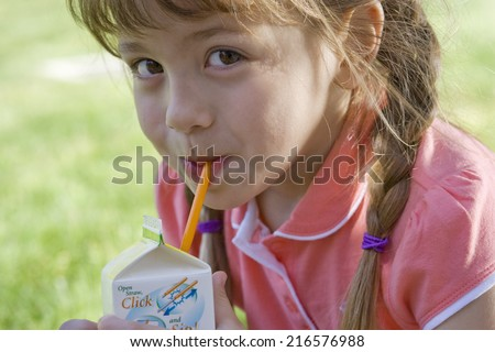 Close up of girl drinking juice from box - stock photo
