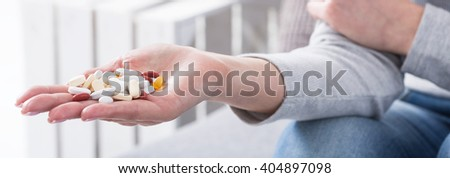 Close-up of girl holding handful full of colorful pills. Woman addicted to medicine - stock photo