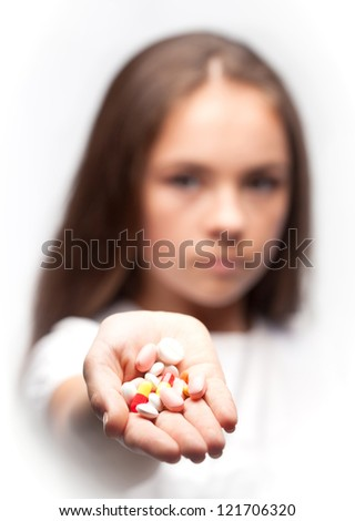 Close up of girl is holding pills - stock photo