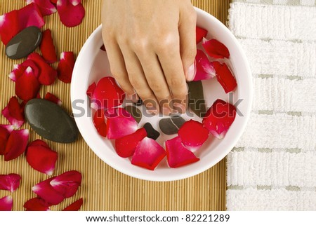 Close-up of girl's hand dropped into a saucer of water near a lot of rose petals. Spa services - stock photo