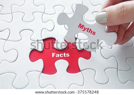 Close up of girl's hand placing the last jigsaw puzzle piece with word Facts and Myths - stock photo
