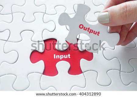 Close up of girl's hand placing the last jigsaw puzzle piece with word Input and Output - stock photo