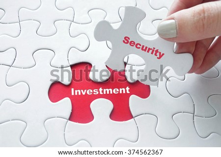Close up of girl's hand placing the last jigsaw puzzle piece with word Investment and Security as Investment Security concept