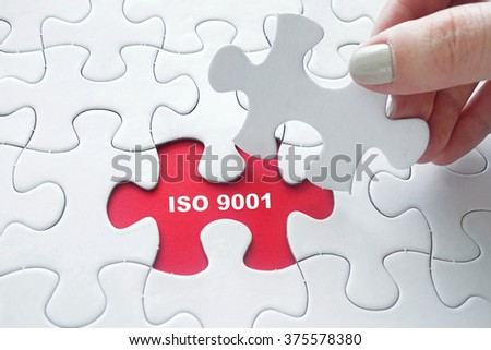Close up of girl's hand placing the last jigsaw puzzle piece with word ISO 9001 - stock photo