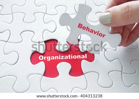 Close up of girl's hand placing the last jigsaw puzzle piece with word Organizational Behavior - stock photo