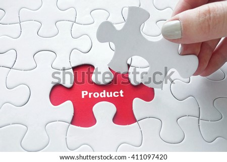 Close up of girl's hand placing the last jigsaw puzzle piece with word Product as business concept - stock photo