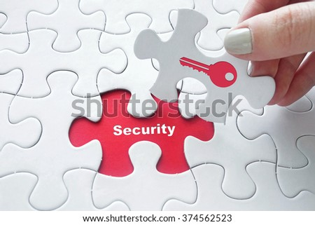 Close up of girl's hand placing the last jigsaw puzzle piece with word security and key icon as security concept