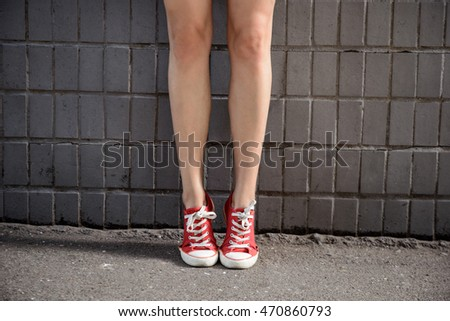 Close up of girl's legs in keds over grey wall.