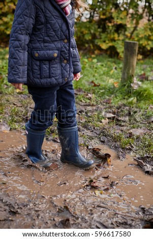 Close Up Of Girl Splashing In Puddle On Winter Walk