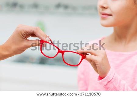 close up of girl taking glasses at optics store - stock photo