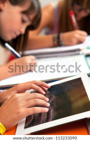 Close up of girls hands typing on tablet at homework session. - stock photo