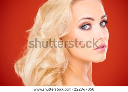 Close Up of Glamorous Blond Woman Looking Over Shoulder Against Red Background - stock photo