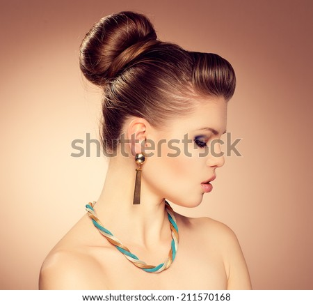 Close-up of glamour Caucasian model with stylish hairdress posing in studio. Young attractive fashionable woman wearing expensive golden earrings and necklace.  - stock photo
