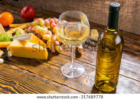 Close Up of Glass and Bottle of White Wine on Rustic Wooden Table with Variety of Cheeses and Grapes with Copy Space in Foreground - stock photo