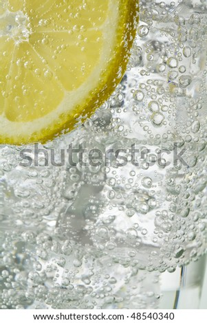 Close up of glass containing sparkling clear liquid and ice cubes and lemon slice - stock photo
