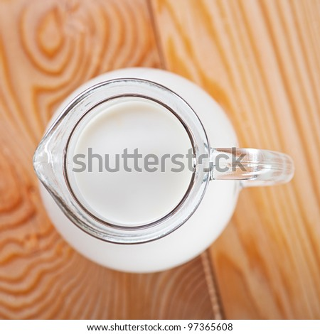 close-up of glass jar filled with transparent milk in wooden kitchen table - stock photo
