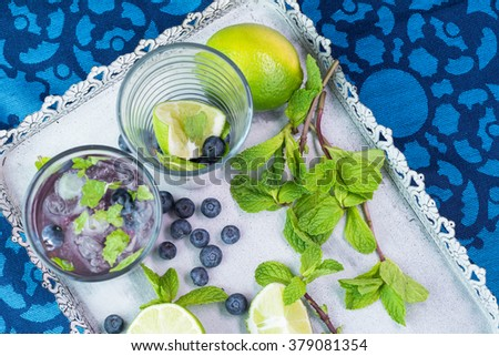 Close up of glass of alcohol cocktail  with blueberries and mint and ingredients on a metal tray.