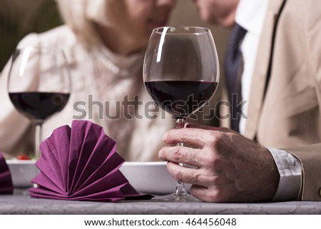 Close-up of glass of red wine hold by senior man during dinner in elegant restaurant with his wife